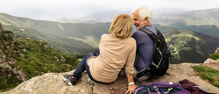 Photo of a couple during their hike with backpacks, reached the top of the mountain