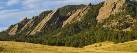 """The early morning light hitting the Boulder Colorado flatirons. The Flatirons are rock formations in Boulder, Colorado consisting of flatirons. There are five large, numbered Flatirons ranging from north to south (First through Fifth, respectively) along the east slope of Green Mountain, and the term """"The Flatirons"""" sometimes refers to these five alone."""